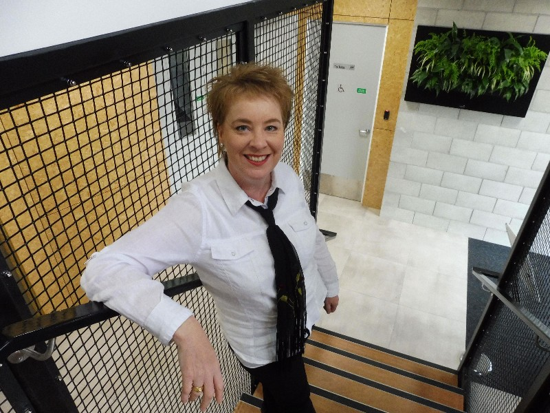 Image of Emma Harding looking up at the camera. She is standing in an office stairwell, wearing black slacks and white blouse.