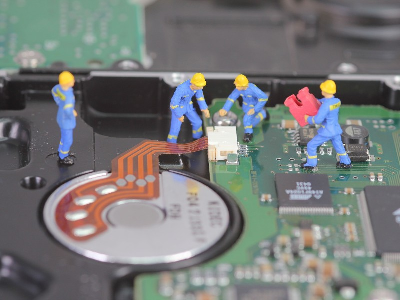 Four miniature figures doing construction work on an uncovered hard drive. They are wearing blue overalls and yellow hard hats.